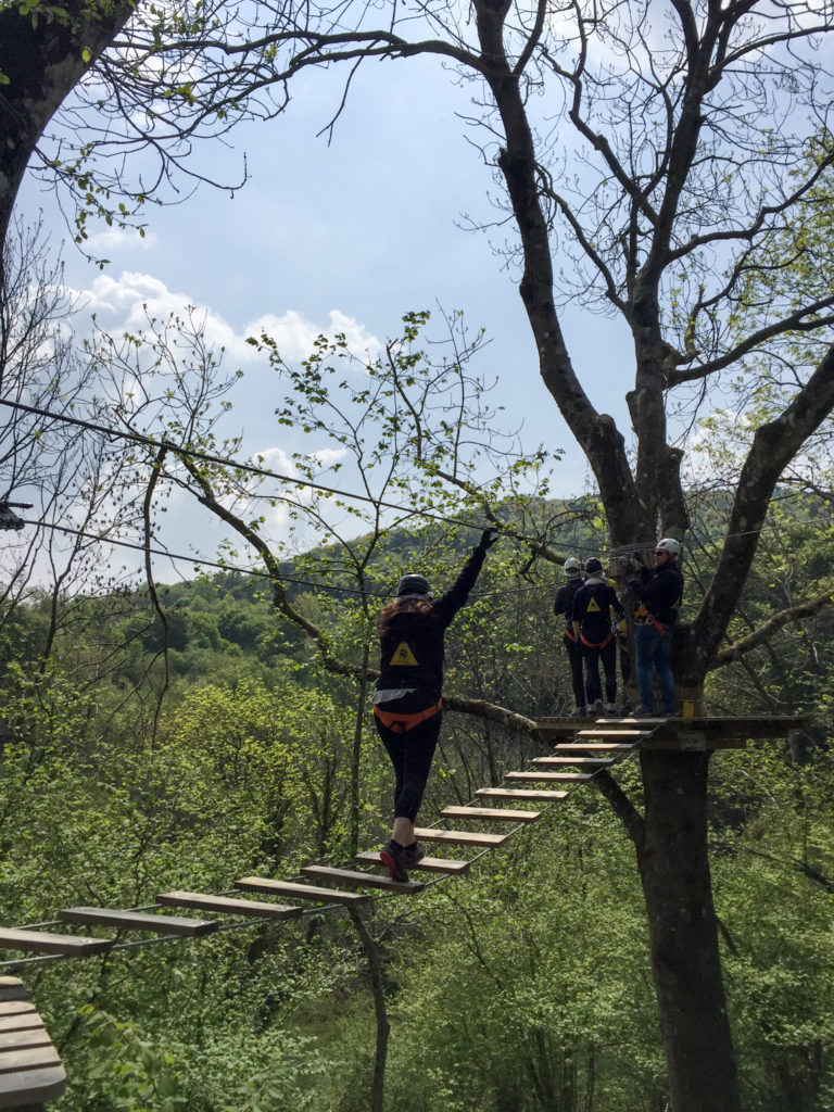 Crossing a rope bridge at Jungle Raider Park Como